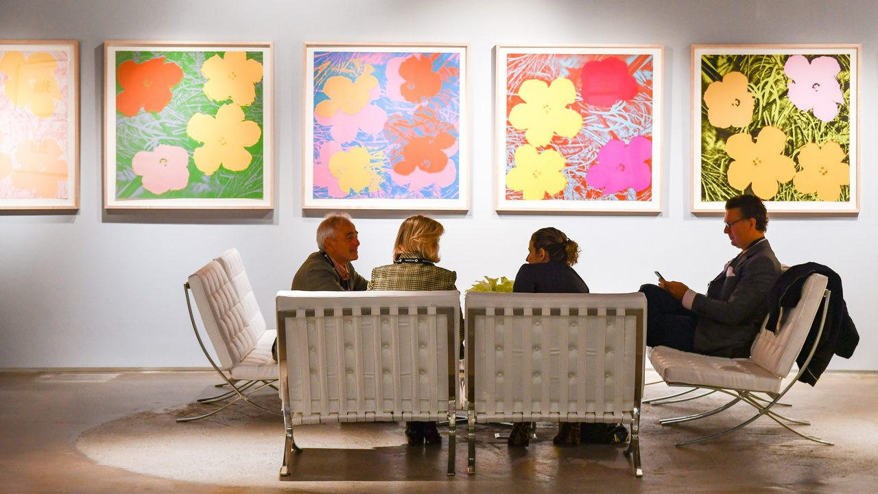 Floral artwork on wall with group discussion