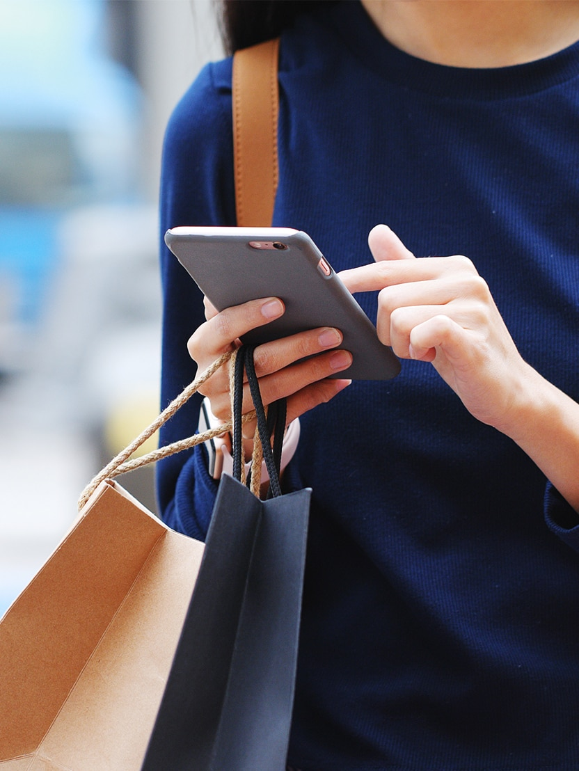 Woman holding paper bag and use of mobile phone