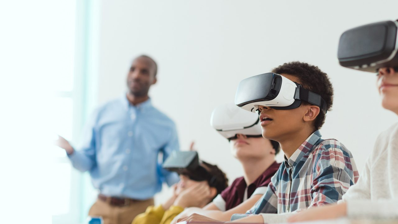 Multicultural school children using virtual reality headsets and teacher standing behind