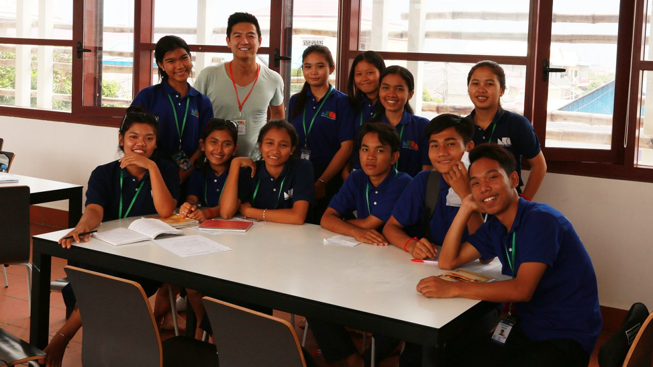 David Sit with school children in a recent visit to Cambodia.