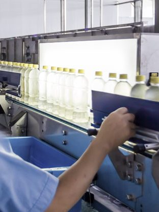 Man quality checking bottles on a conveyor