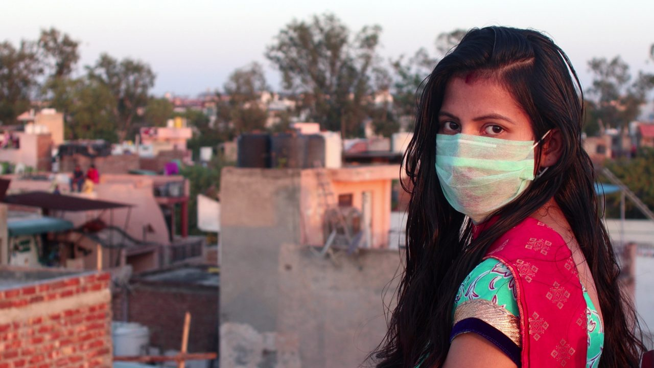 A lady in a surgical mask looking back at the camera