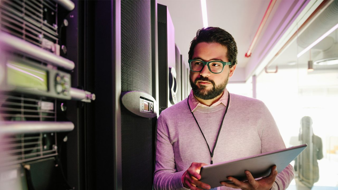 Focused male IT technician with digital tablet working in network server room